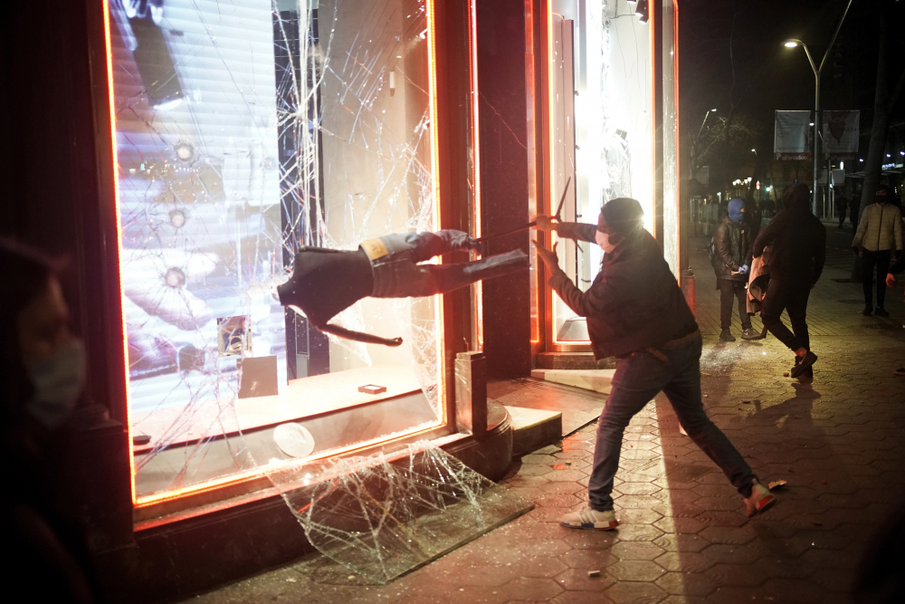 A demonstrator smashes a shop window during a protest condemning the arrest of rap singer Pablo Hasél in Barcelona, Spain, on Saturday.