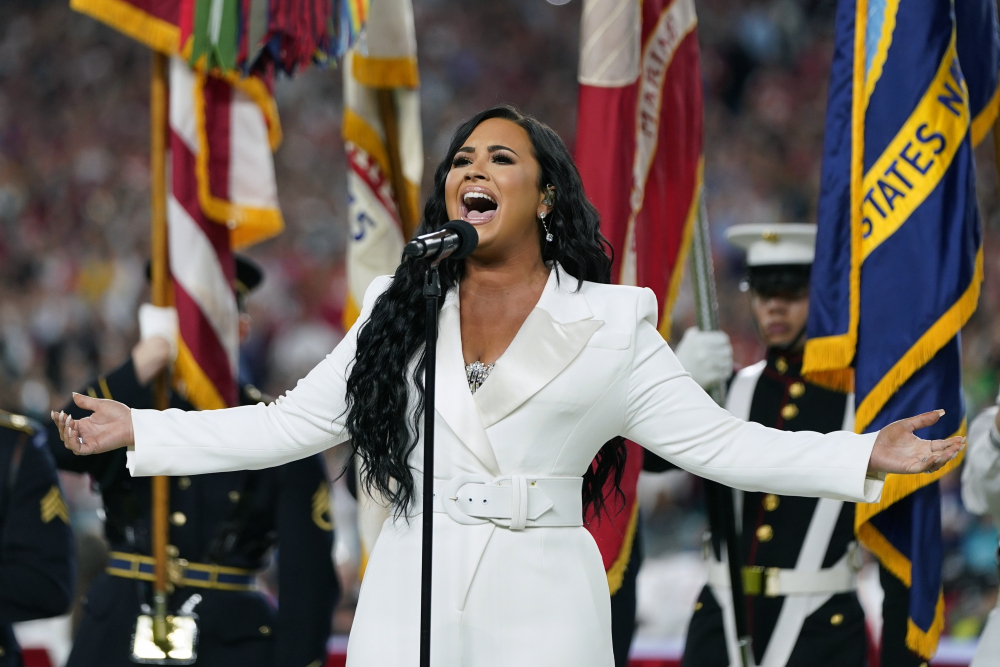 """Demi Lovato performs the national anthem before the NFL Super Bowl 54 in Miami Gardens, Fla., in 2020. Lovato reveals publicly for the first time details about her near-fatal drug overdose in 2018 in """"Demi Lovato: Dancing With the Devil,"""" a four-part docuseries debuting March 23, 2021, on YouTube Originals."""