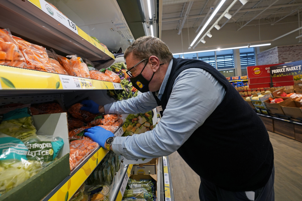 Joseph Lupo, an employee of the grocery chain Lidl, arranges carrots in the produce aisle at the grocery market where he works in Lake Grove, N.Y. on Thursday, Feb. 4, after getting vaccinated against coronavirus earlier in the day. The German grocery chain is offering a $200 financial incentive all workers who get vaccinated against COVID-19. Lupo, a Lidl supervisor who fell ill with the virus in March, was elated to get his first vaccine dose.