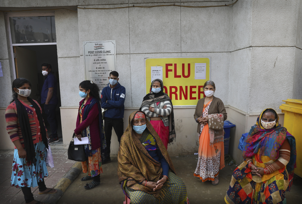 People wait outside a health center to get tested for COVID-19 in New Delhi, India, on Thursday.