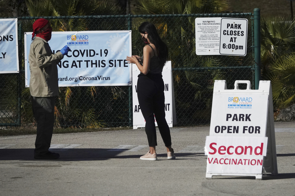 A woman asks directions at the entrance to Vista View Park in Davie, Fla., where a COVID-19 vaccination site has opened for second doses. (Joe Cavaretta/South Florida Sun-Sentinel via AP, File)