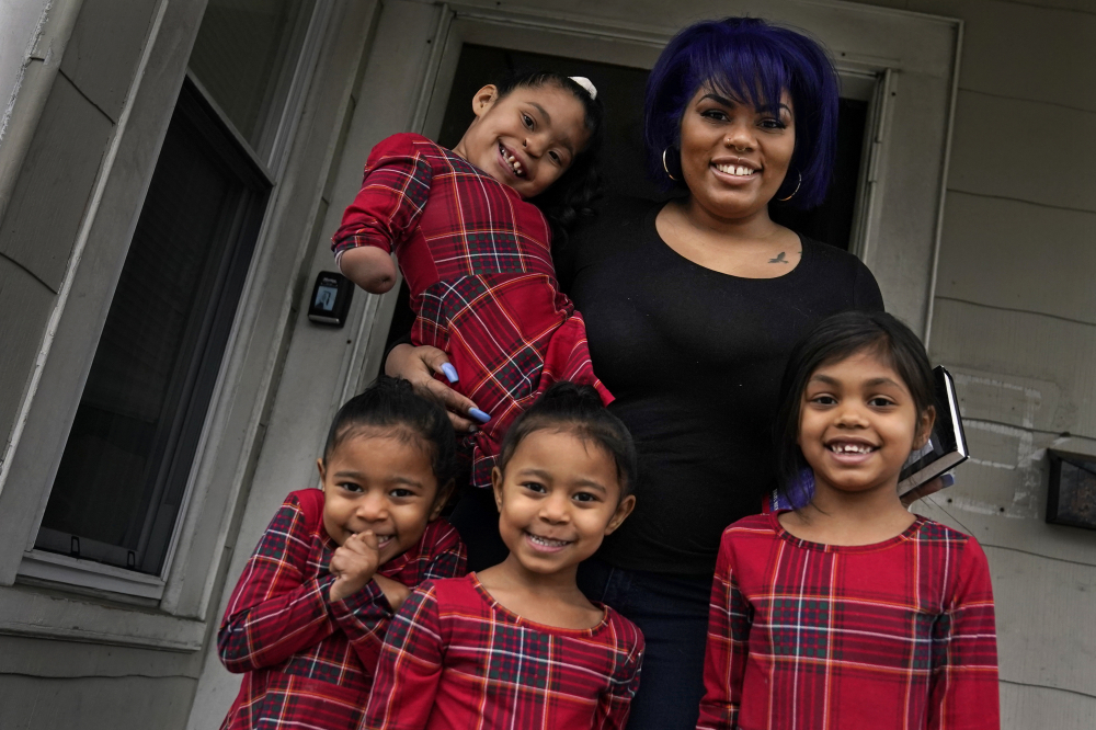 Dinora Torres, a MassBay Community College student, poses with her four daughters on the front porch of their home Jan. 14 in Milford, Mass. From front left are Davina, Alana and Hope, with Faith in Dinora's arms.