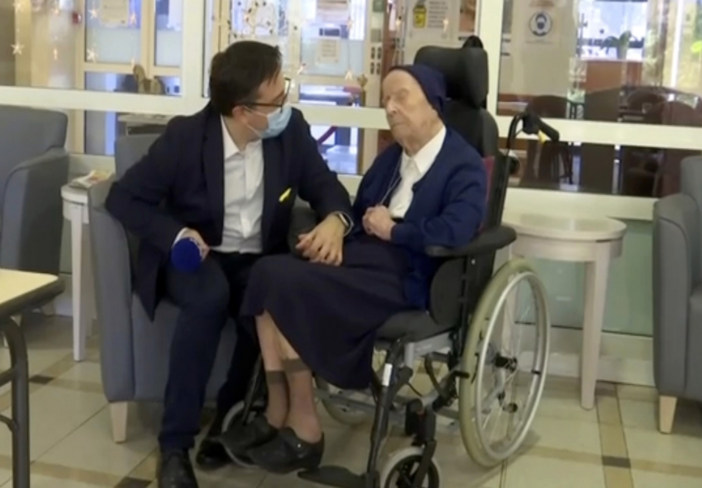 Sister Andre is interviewed by an official at the Sainte Catherine Laboure Nursing Home in Toulon, France, on Tuesday. The 116-year-old nun tested positive for COVID-19 virus in mid-January but just three weeks later she is fit as a fiddle – albeit it in her regular wheelchair.