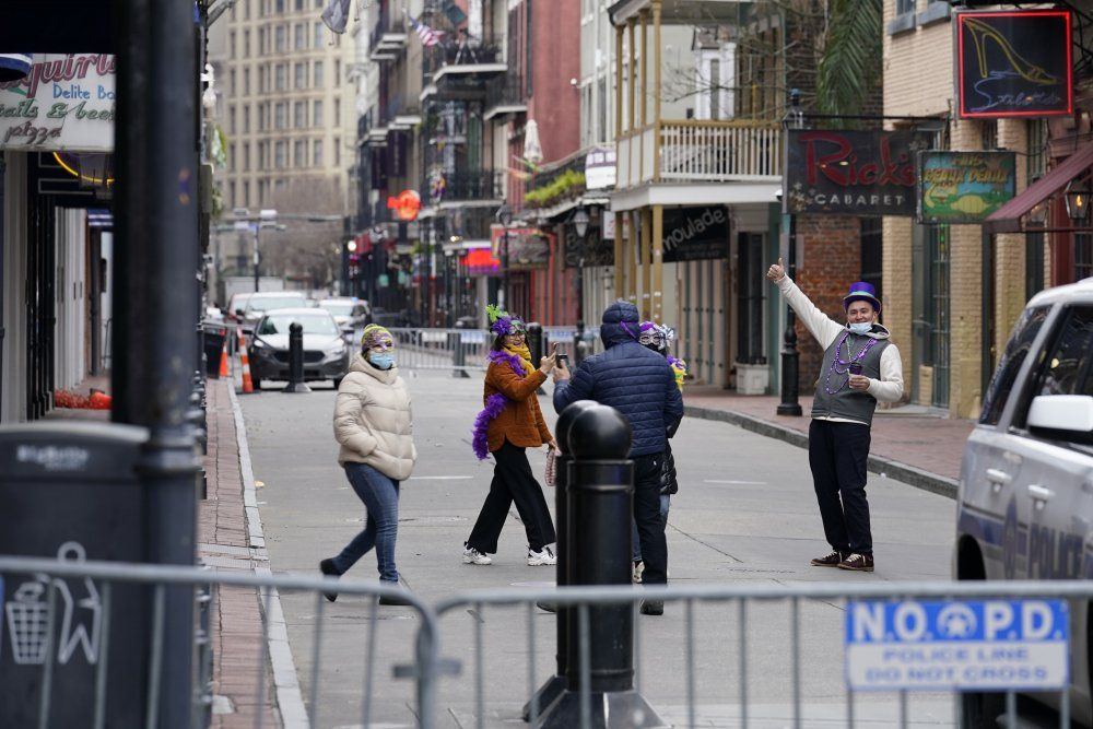 Tourists take photos on a nearly deserted Bourbon Street during Mardi Gras in the French Quarter of New Orleans on Tuesday.