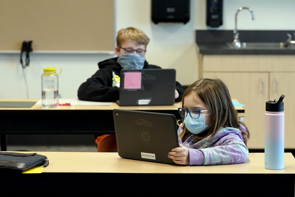 Students work in a fourth-grade classroom at Elk Ridge Elementary School in Buckley, Wash., this month. Amid mounting tensions about school reopening, the Centers for Disease Control and Prevention released long-awaited guidance on Friday.