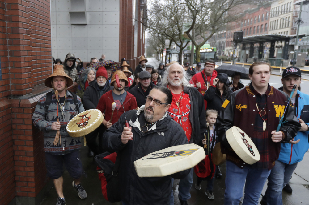 """Tony A. """"Naschio"""" Johnson, center, elected chairman of the Chinook Indian Nation, plays a drum as he leads tribal members and supporters as they march to the federal courthouse in Tacoma, Wash., on Jan. 6, 2020."""