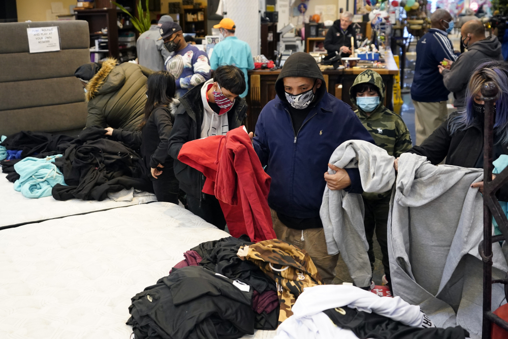 People select shirts and sweatshirts being given away at a Gallery Furniture store Tuesday after the owner opened his business as a shelter for those without power at their homes in Houston.