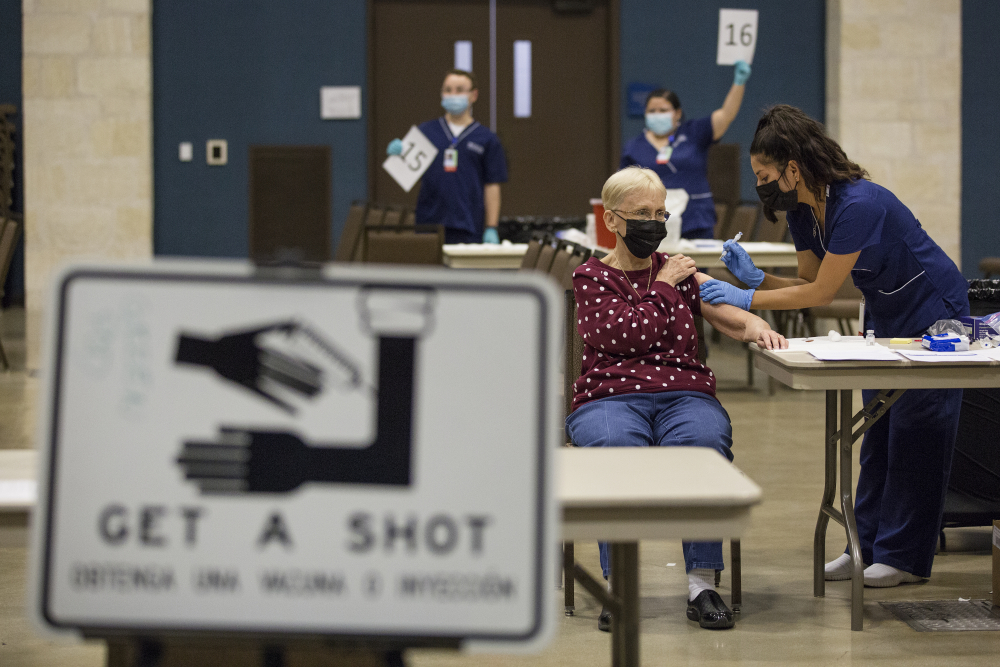 Edna Becker receives the Moderna coronavirus vaccine from nurse Patricia Torres at the mass vaccination clinic at the New Braunfels Civic/Convention Center in New Braunfels, Texas, in January. Some governors, public health directors and committees advising them are holding key discussions behind closed doors, including debates about who should be eligible for the shots and how to best distribute them.