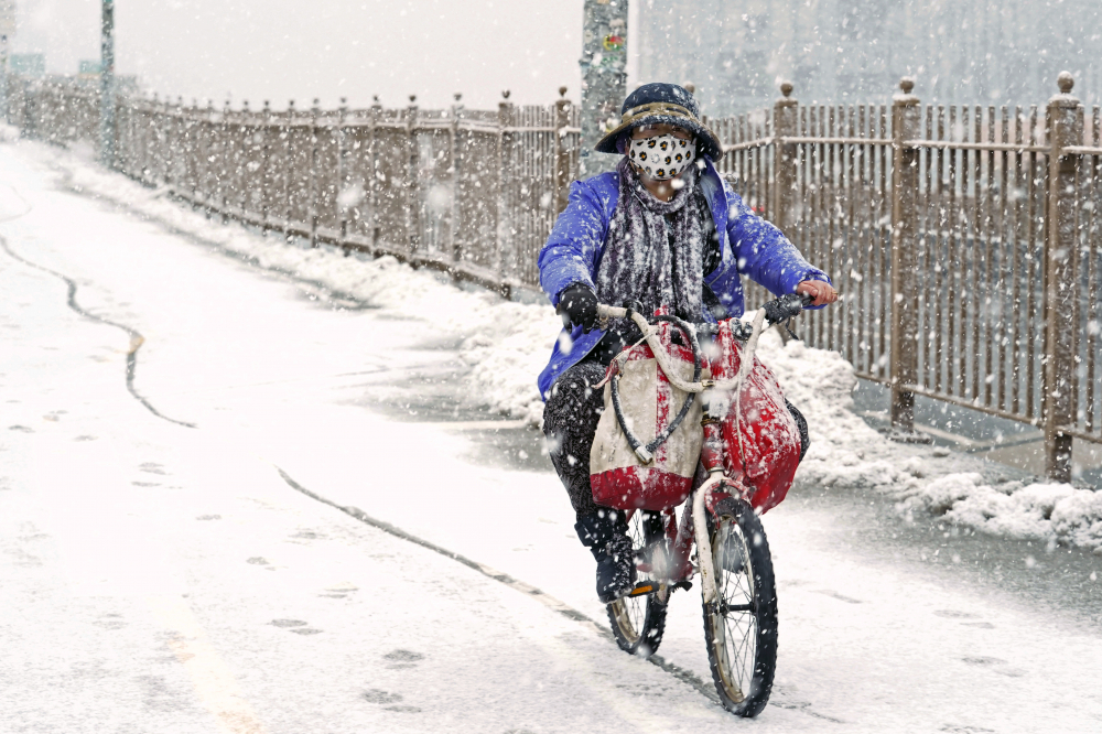 A woman rides a bicycle across the Brooklyn Bridge during Sunday's snow in the Brooklyn borough of New York. It was the second time in less than a week the area has been buffeted by heavy snowfall. (AP Photo/Kathy Willens)
