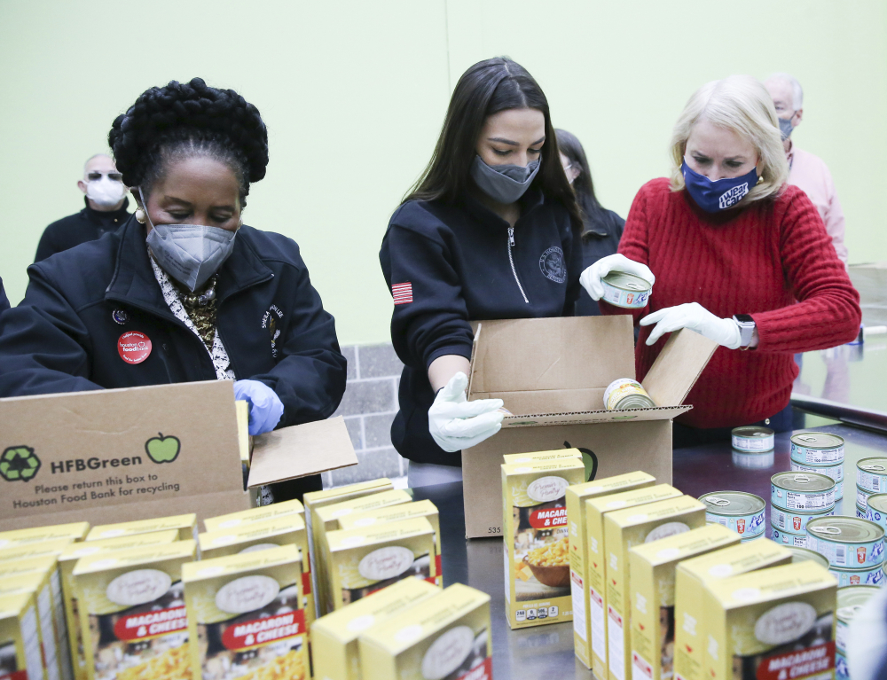 From left, U.S. Reps. Sheila Jackson Lee,  Alexandria Ocasio-Cortez  and Sylvia Garcia fill boxes at the Houston Food Bank on Saturday.