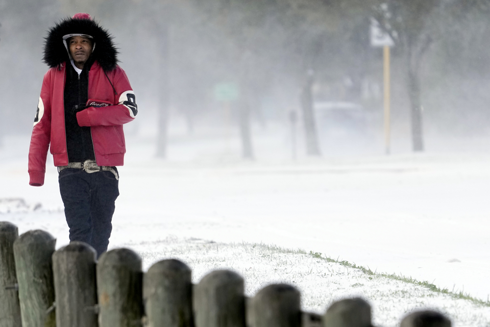 Igee Cummings walks through the snow Monday, Feb. 15, in Houston. A winter storm dropping snow and ice sent temperatures plunging across the southern Plains, prompting a power emergency in Texas a day after conditions canceled flights and impacted traffic across large swaths of the U.S.