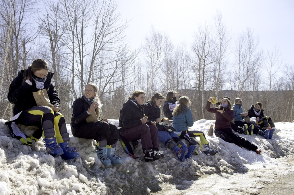 Members of the Maranacook Community High School girls Alpine ski team from Readfield eat lunch Thursday on a snowbank at Black Mountain of Maine in Rumford. The Black Bears were one of 11 teams competing in the Kennebec Valley Athletic Conference championships. The team placed second behind Mt. Blue High School of Farmington.