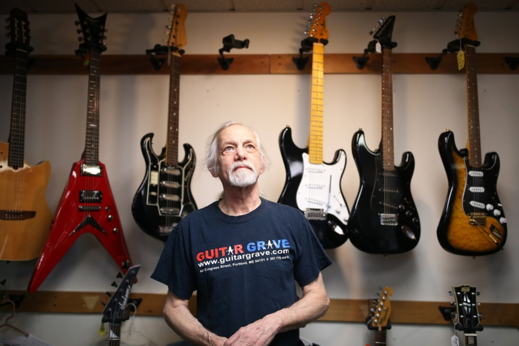 SOUTH PORTLAND, ME - MARCH 8: Mike Fink, owner of Guitar Grave, stands next to his inventory of guitars at his South Portland shop on Monday. (Staff photo by Ben McCanna/Staff Photographer)