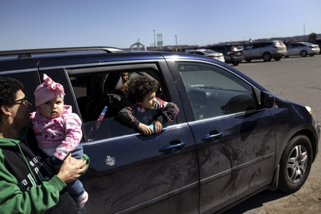Keston Johnson-McDonnell, 6, sticks his head out the window of his family's 2005 minivan at Bug Light Park in South Portland on Wednesday, March 17, 2021. The family is buying a new, more reliable vehicle with the help of the stimulus money they are receiving.