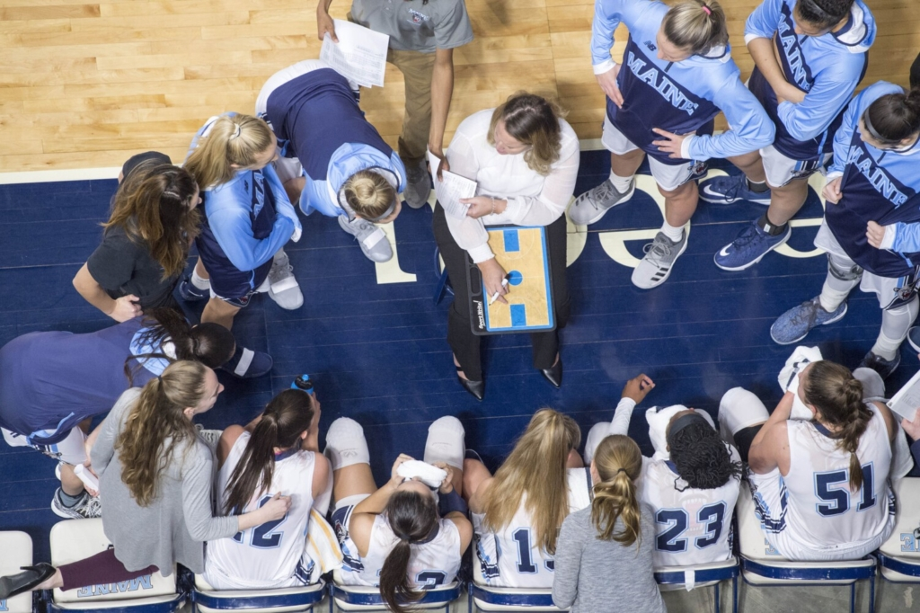 University of Maine head coach Amy Vachon huddles with her players during a timeout. The 2020-21 team had the highest grade-point average of any women's basketball team in the nation.