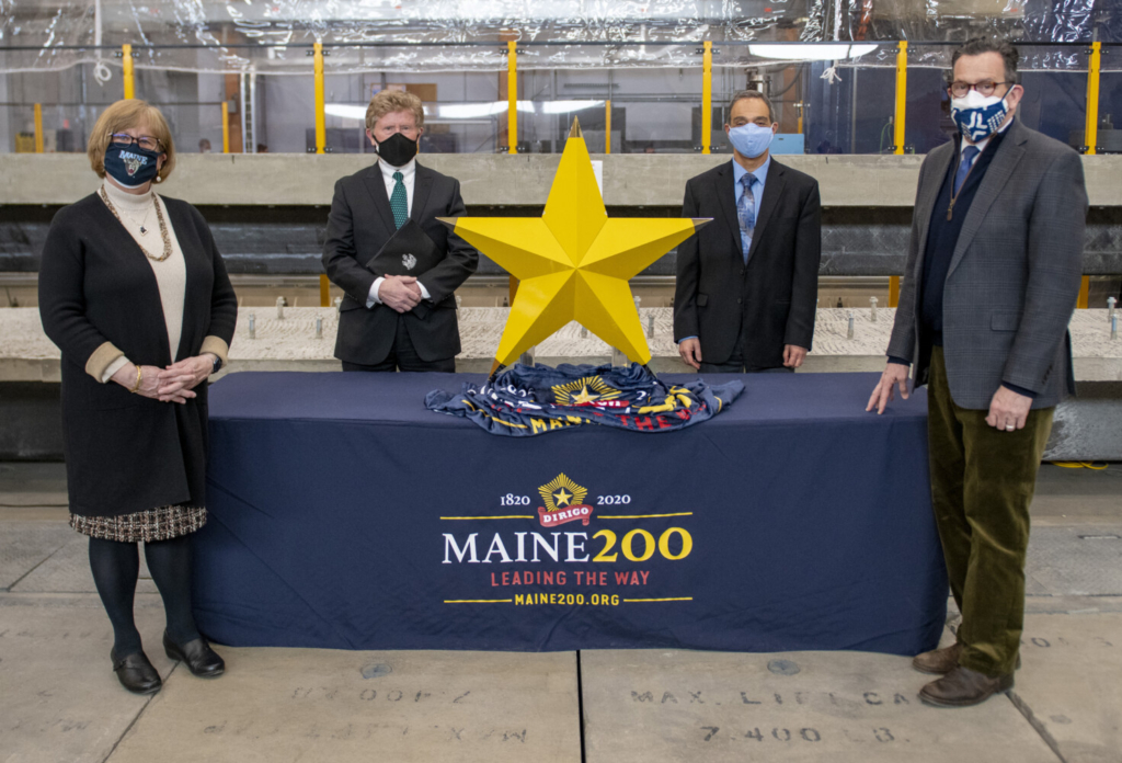 University of Maine presents 3D-printed Dirigo Star to the Maine Bicentennial Commission for Maine Bicentennial Time Capsule. On hand for the presentation, from left to right, are Joan Ferrini-Mundy, University of Maine System vice chancellor for research and innovation, and UMaine president; Sen. Bill Diamond, chairman of the Maine Bicentennial Commission; Habib Dagher, executive director of the UMaine Advanced Structures and Composites Center; and Dannel Malloy, UMS chancellor.