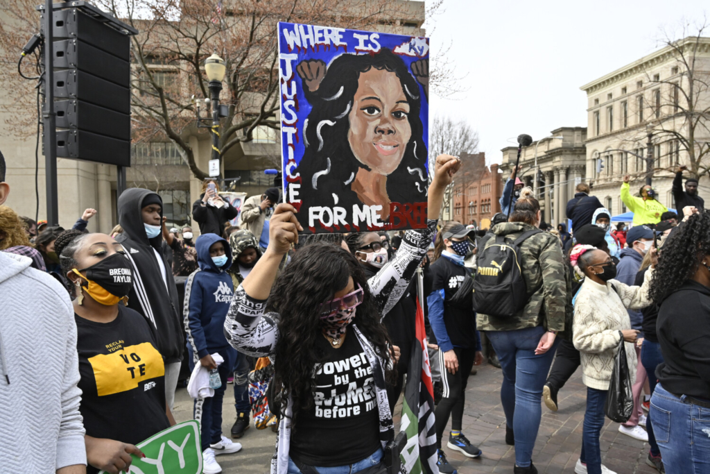 A protester displays a painting of Breonna Taylor during a rally on the one-year anniversary of her death at Jefferson Square Park in Louisville, Ky., on Saturday.