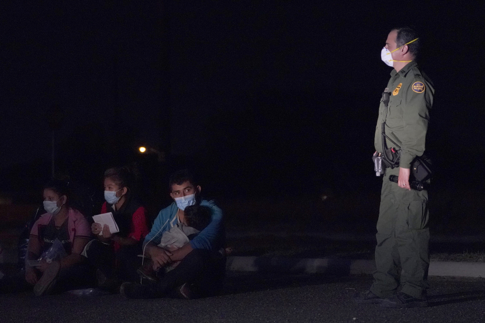 A migrant man holds a child as he looks at a U.S. Customs and Border Protection agent at an intake area after crossing the U.S.-Mexico border, early Wednesday in Roma, Texas. A surge of migrants on the Southwest border has the Biden administration on the defensive.