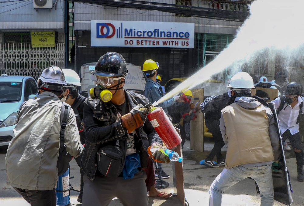 Anti-coup protesters discharge fire extinguishers to counter the impact of the tear gas fired by police during a demonstration Thursday in Yangon.