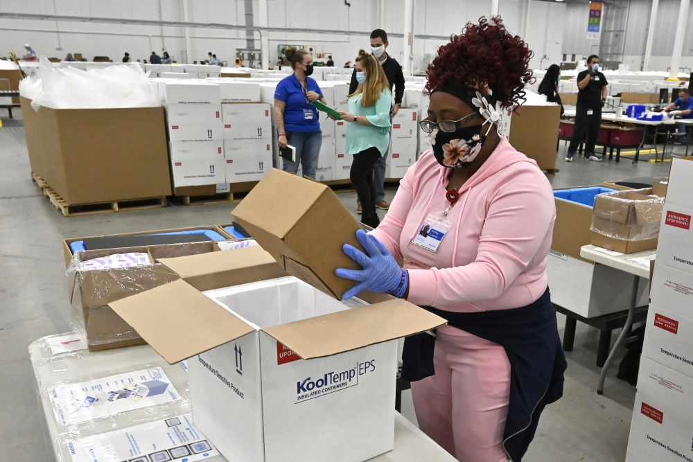 An employee with the McKesson Corporation packs a box of the Johnson & Johnson COVID-19 vaccine into a cooler for shipping from their facility Monday in Shepherdsville, Ky.