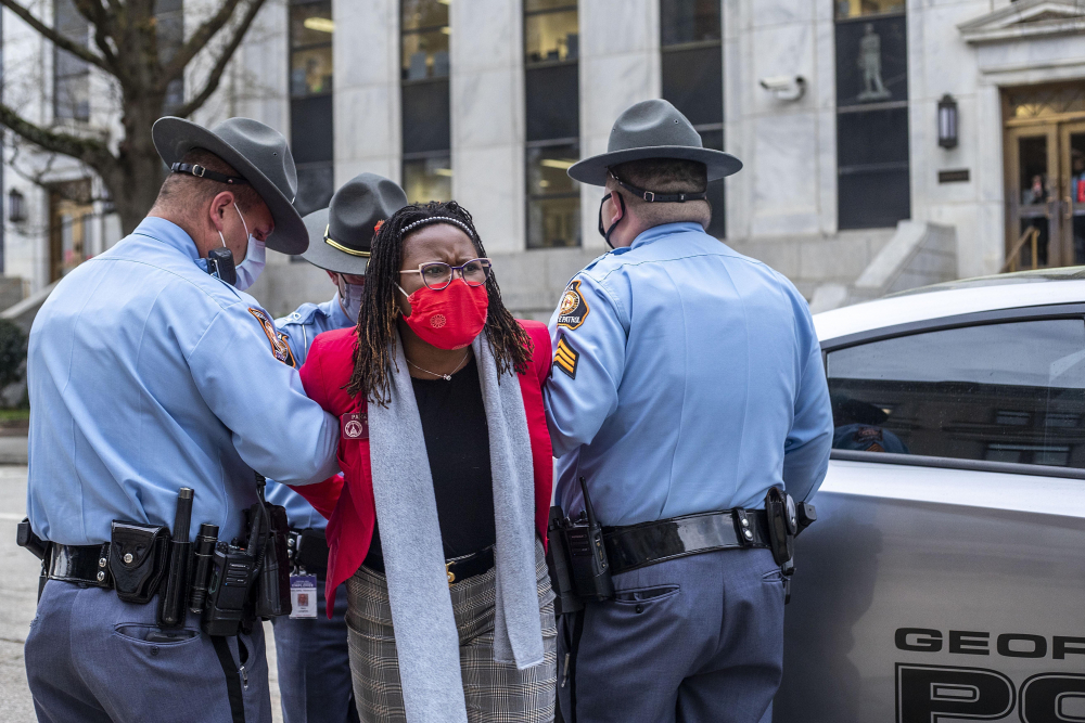 State Rep. Park Cannon, D-Atlanta, is placed into the back of a Georgia State Capitol patrol car after being arrested by at the Georgia State Capitol Building in Atlanta on March 25. Cannon was arrested by Capitol police after she attempted to knock on the door of Gov. Brian Kemp's office during his remarks after he signed into law a sweeping Republican-sponsored overhaul of state elections that includes new restrictions on voting by mail and greater legislative control over how elections are run.