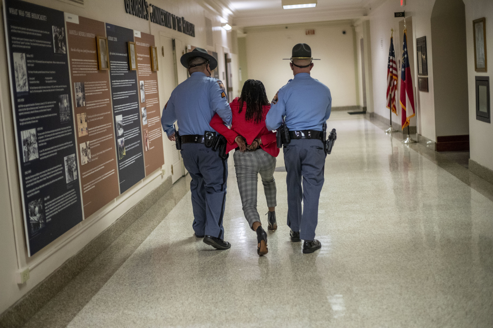 "Georgia Rep. Park Cannon, D-Atlanta, is escorted out of the Georgia Capitol by Georgia state troopers after being asked to stop knocking on a door that lead to Gov. Brian Kemp's office while Kemp was speaking after signing a sweeping overhaul of state elections behind closed doors in Atlanta on Thursday. An attorney for Cannon says it's ""law enforcement overreach"" to charge the Georgia House member with two felonies."