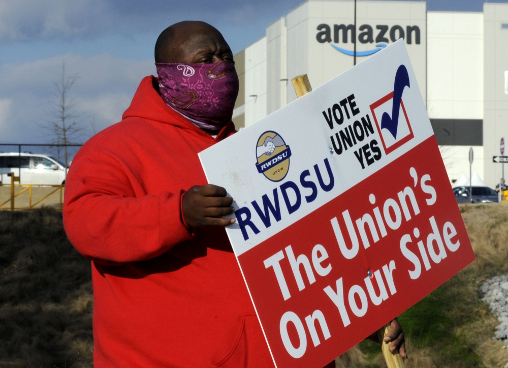 Michael Foster of the Retail, Wholesale and Department Store Union holds a sign outside an Amazon facility where labor is trying to organize workers on Tuesday, Feb. 9. For Amazon, a successful effort could motivate other workers to organize.