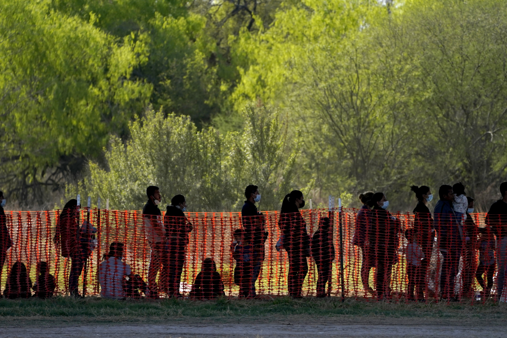 Migrants are in custody Friday at a U.S. Customs and Border Protection processing area under the Anzalduas International Bridge in Mission, Texas.