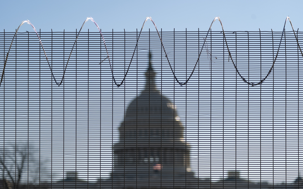 "Fencing and razor wire surround the perimeter of the U.S. Capitol in Washington last month.  Acting Capitol Police chief Yogananda Pittman said her investigators had collected ""some concerning intelligence"" about a possible plot to try to breach the Capitol again on Thursday."