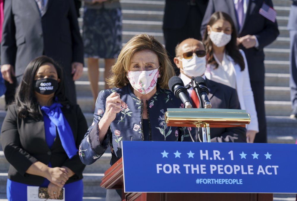 Speaker of the House Nancy Pelosi, D-Calif., and the Democratic Caucus gather to address reporters on H.R. 1, the For the People Act of 2021, at the Capitol in Washington on Wednesday. House Democrats are expected to pass the sweeping elections and ethics bill.