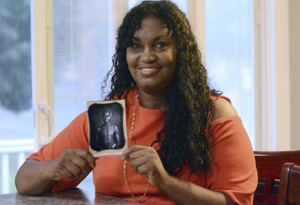 Tamara Lanier holds an 1850 photograph July 17, 2018, at her home in Norwich, Conn., of a South Carolina slave named Renty, who Lanier said is her family's patriarch. The portrait was commissioned by Harvard biologist Louis Agassiz, whose ideas were used to support the enslavement of Africans in the United States.