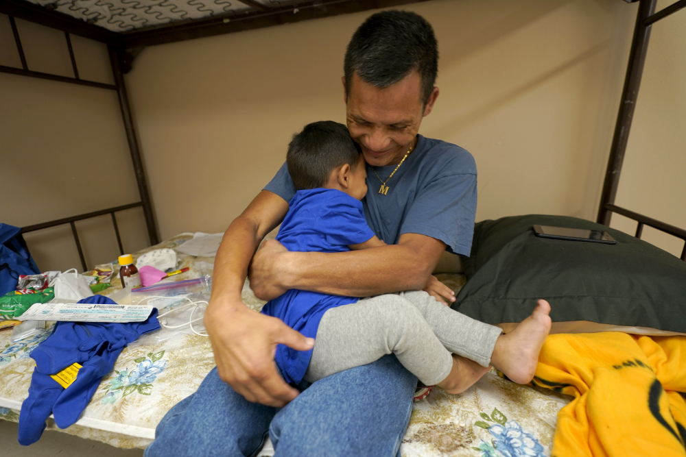 Elmer Maldonado, top, a migrant from Honduras, hugs his 1-year-old son at a shelter, Monday in Harlingen, Texas. They spent a week in immigration custody after crossing the Rio Grande through Texas to request asylum. His experience illustrates a cycle that is repeating itself thousands of times a week amid a dramatic rise in migrant children and families at the U.S.-Mexico border: They arrive in the middle of the night by the dozens and are kept at outdoor intake sites, then taken to overcrowded detention facilities well past the 72-hour court-imposed limit.