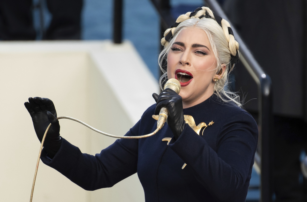 Lady Gaga, shown singing the national anthem during President-elect Biden's inauguration at the U.S. Capitol in Washington, was in Rome filming a movie when her dog walker was shot by two men who took off with two of her dogs. The dog walker is recovering and the dogs were returned.