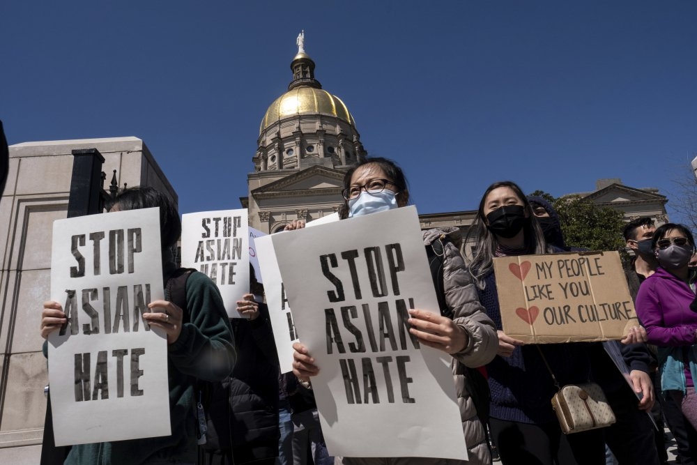 """People hold signs while participating in a """"stop Asian hate"""" rally outside the Georgia State Capitol in Atlanta on Saturday afternoon, March 20."""