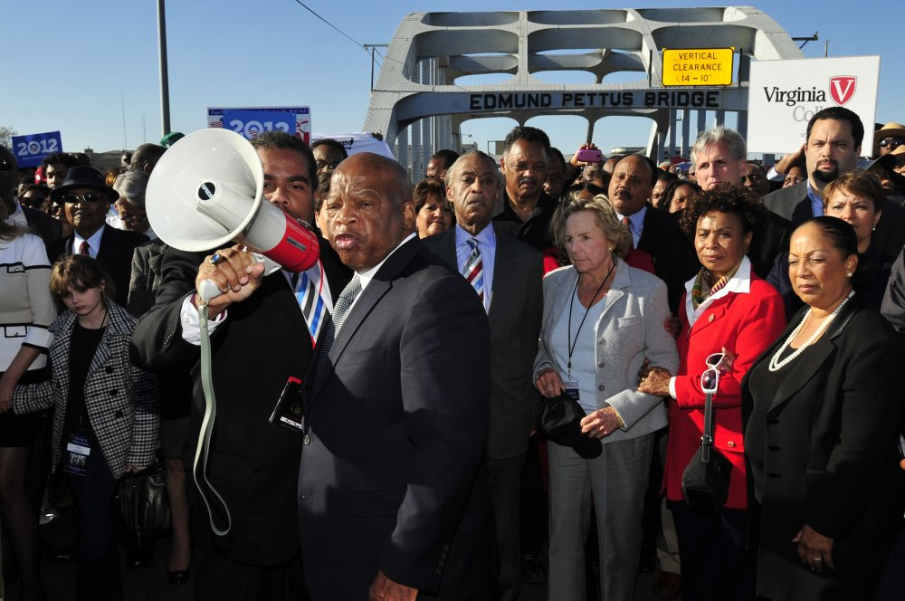 """U.S. Rep. John Lewis, D-Ga., center, talks with those gathered on the historic Edmund Pettus Bridge during the 19th annual reenactment of the """"Bloody Sunday"""" Selma to Montgomery civil rights march across the bridge in Selma, Ala., on March 4, 2012."""