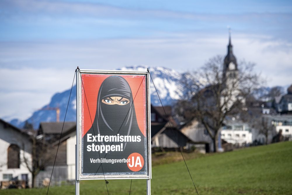 A poster supporting the initiative 'Yes to a ban on covering the face' is displayed at the Swiss village Buochs. One Sunday, voters approved a long-laid proposal to ban face-coverings like niqabs and burqas worn by some Muslim women or by protesters in ski masks or bandanas.