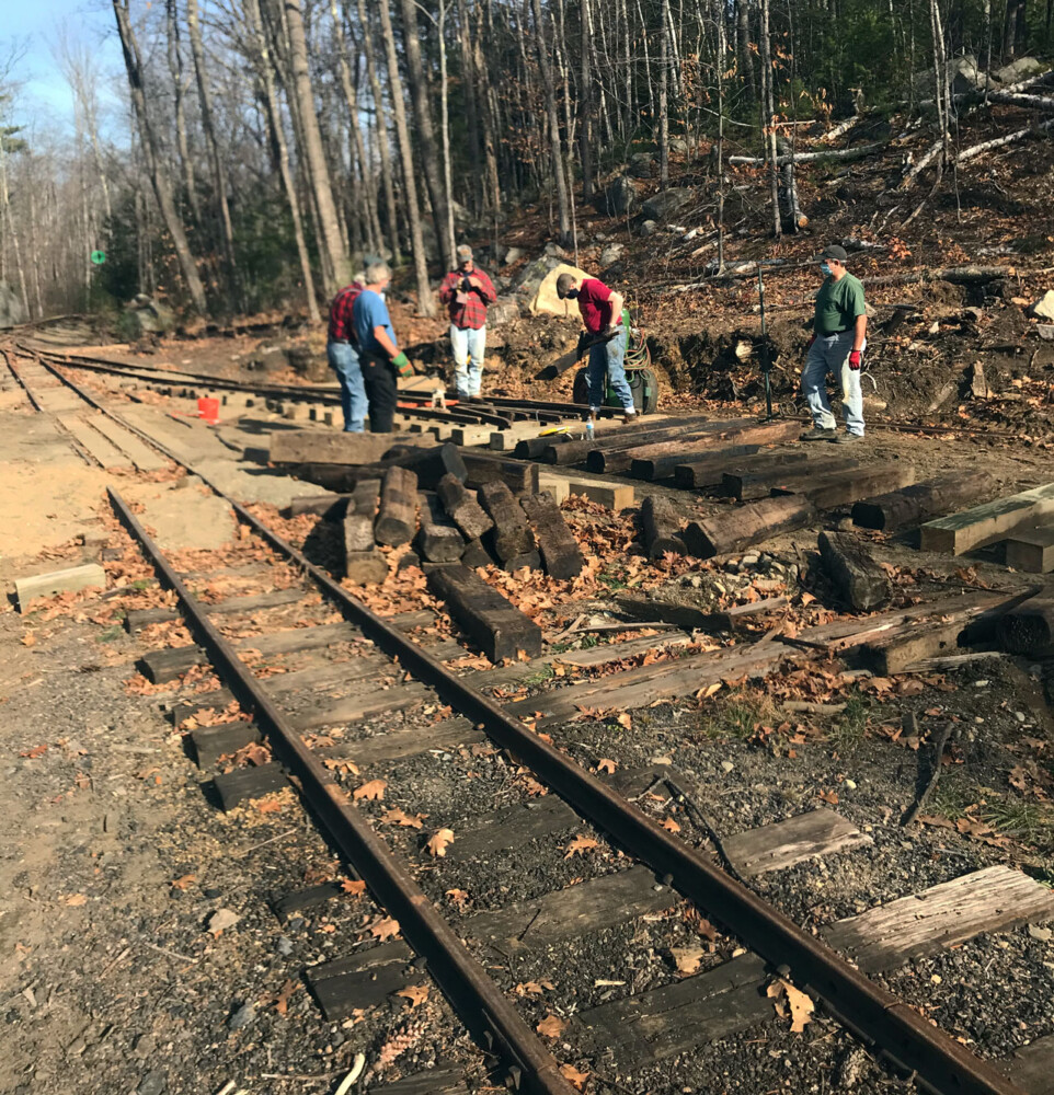 Sandy River and Rangeley Lakes Railroad  and Wiscasset, Waterville and Farmington Railway volunteers work together to lay track on Nov. 7, 2020 in Phillips.
