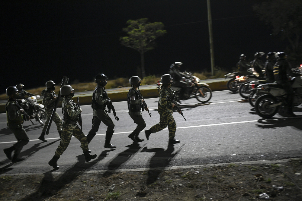 Security forces take part in a military drill to mark the eighth anniversary of President Hugo Chavez's death in Caracas, Venezuela, on Friday. The country's economy has been struggling the past few years and an estimated 5 million people have fled, mostly to neighboring countries such as Colombia, but many have settled in South Florida.