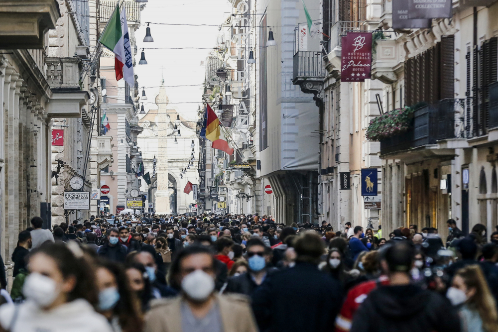 People crowd Via del Corso shopping street Feb. 7 in Rome, following the ease of restriction measures to curb the spread of COVID-19.