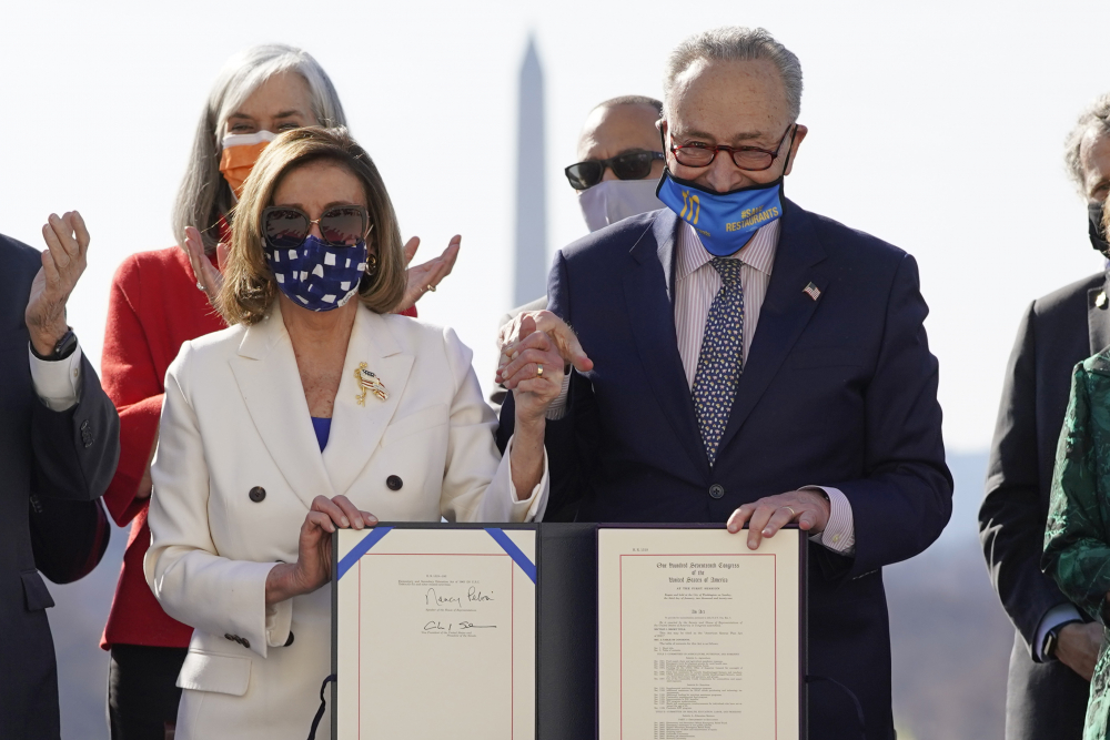 House Speaker Nancy Pelosi of California and Senate Majority Leader Chuck Schumer of New York finish signing the $1.9 trillion COVID-19 relief bill during an enrollment ceremony on Capitol Hill on Wednesday in Washington.