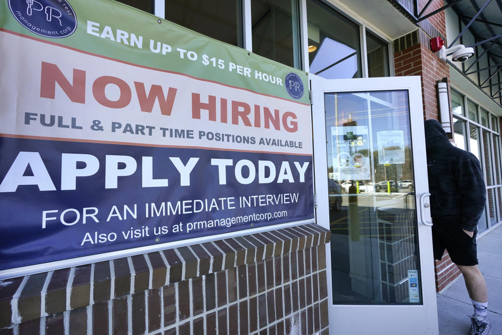 """A man walks into a restaurant displaying a """"Now Hiring"""" sign on Thursday in Salem, N.H.  U.S. employers added a robust 379,000 jobs last month, the most since October and a sign that the economy is strengthening as confirmed viral cases drop, consumers spend more and states and cities ease business restrictions."""