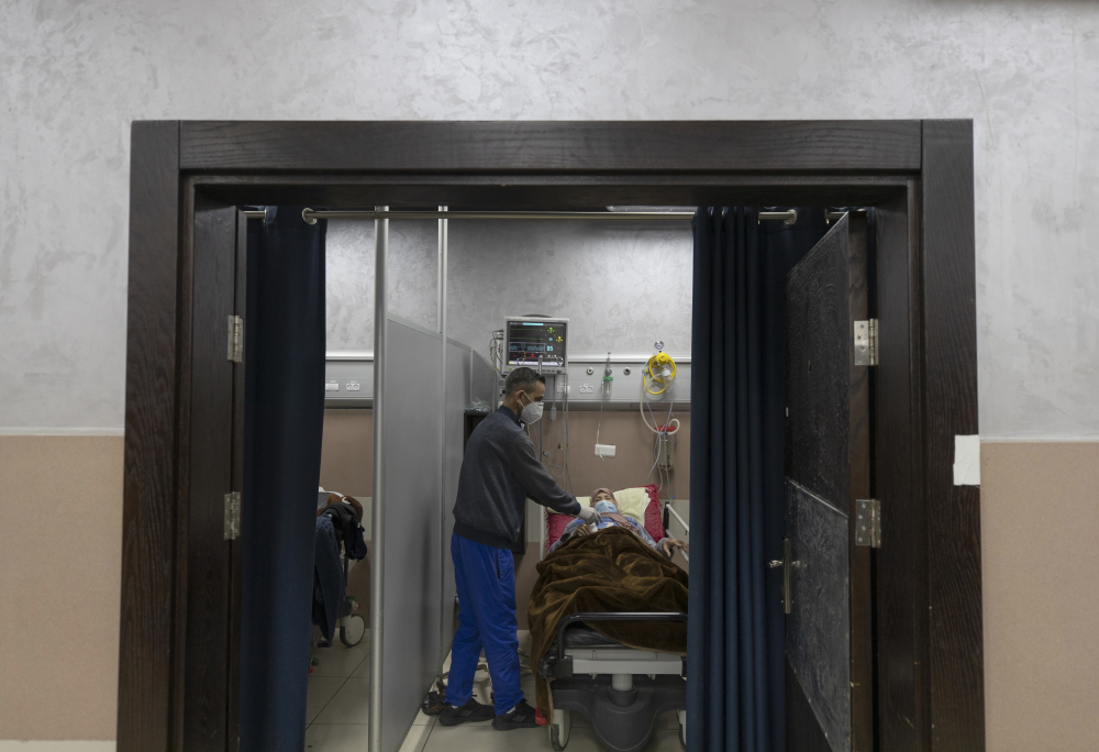 A medical staffer attends to a Palestinian patient infected with COVID-19 at the Palestine Medical Complex in the West Bank city of Ramallah on Tuesday. The Palestinian Authority has reported more than 130,000 cases in the West Bank since the outbreak began.