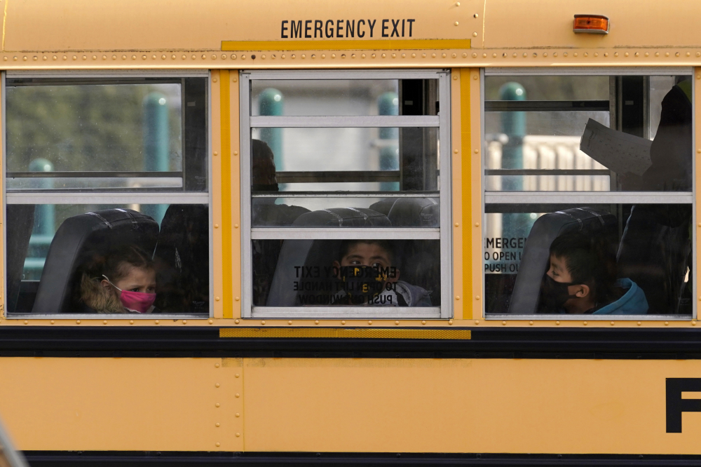 Elementary school students sit on board a school bus after attending in-person classes at school in Wheeling, Ill. in November 2020. The latest federal relief package includes $81 billion that began flowing to states in late March 2021 with the goal of helping schools reopen quickly.