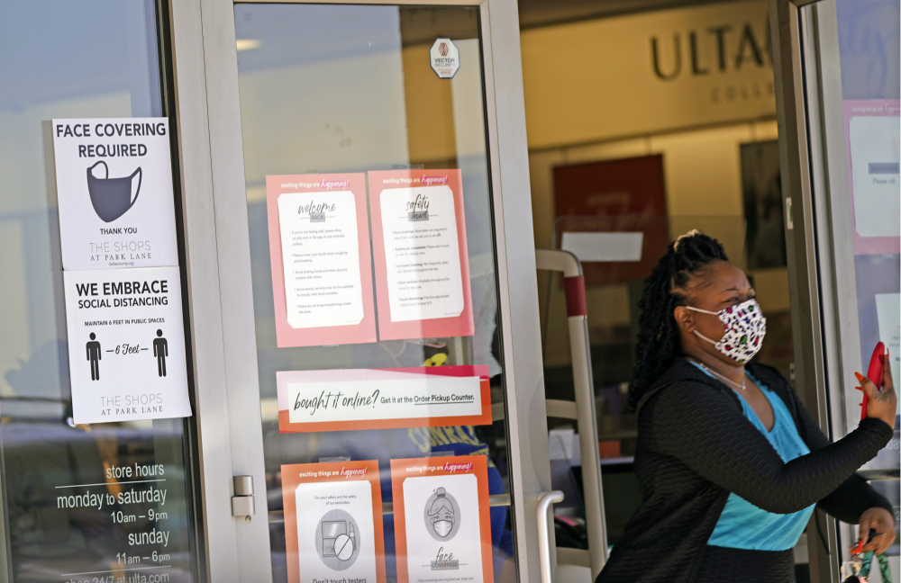 A customer exits a store with a mask required sign displayed, Tuesday, March 2, in Dallas.