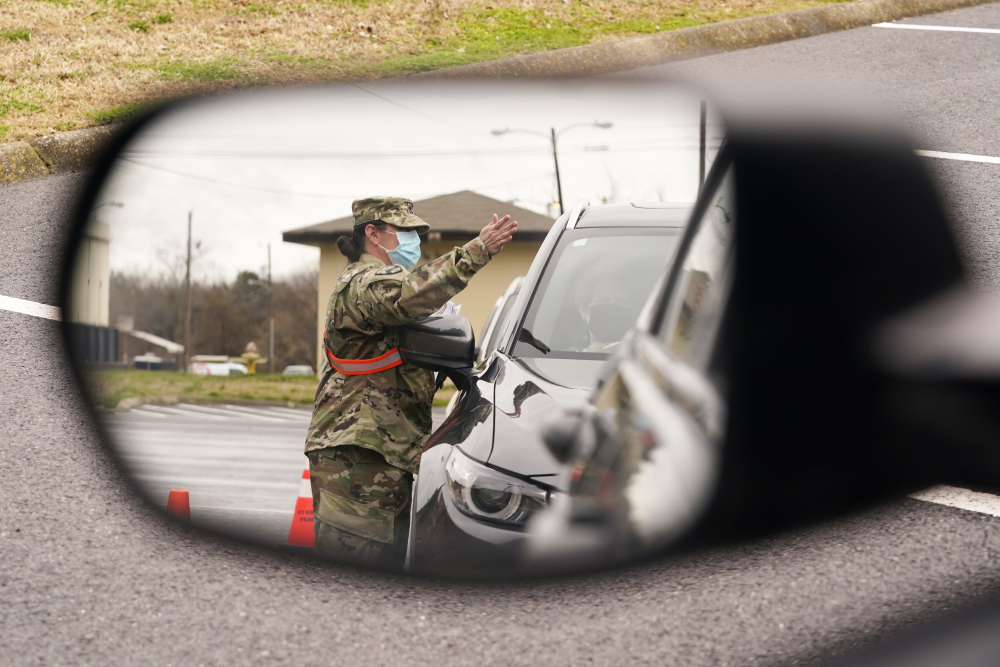 A National Guard soldier directing drivers is reflected in the mirror of a car waiting in a COVID-19 vaccination line Feb. 26 in Shelbyville, Tenn. Tennessee has continued to divvy up vaccine doses based primarily on how many people live in each county, and not on how many residents belong to eligible groups within those counties.