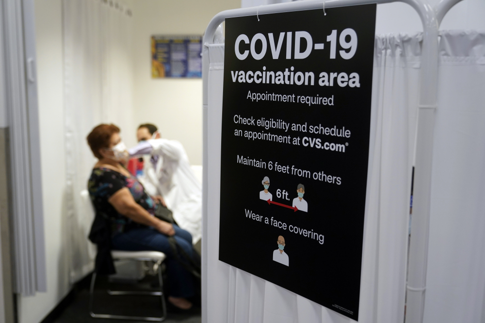 A patient receives a shot of the Moderna COVID-19 vaccine next to a guidelines sign at a CVS Pharmacy branch in Los Angeles on Monday. More than 28 million Americans fully vaccinated against the coronavirus will have to keep waiting for guidance from U.S. health officials for what they should and shouldn't do.