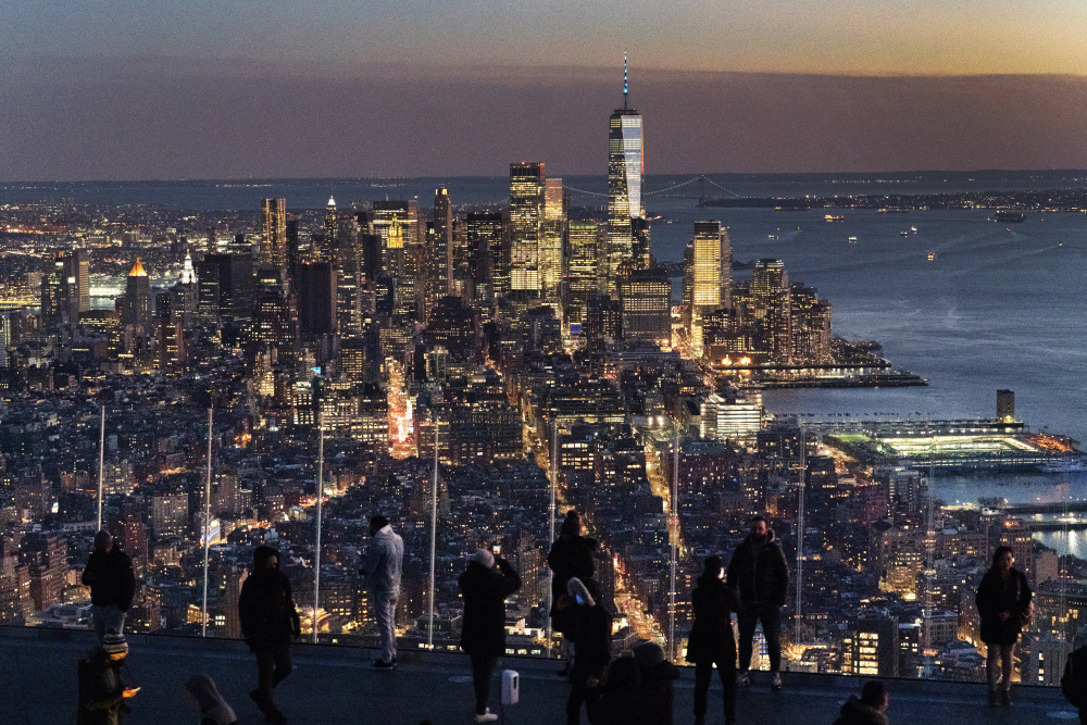 Visitors to the Edge, an outdoor observation deck 1100 feet above the ground, look at the lights of Manhattan, March 2, 2021, in New York.