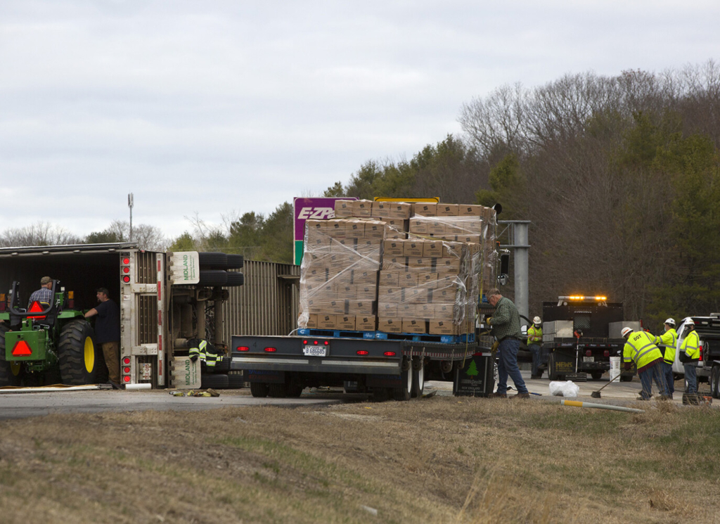 Frozen hash browns are offloaded from overturned tractor trailer at Exit 11 ramp in Falmouth on Thursday morning.