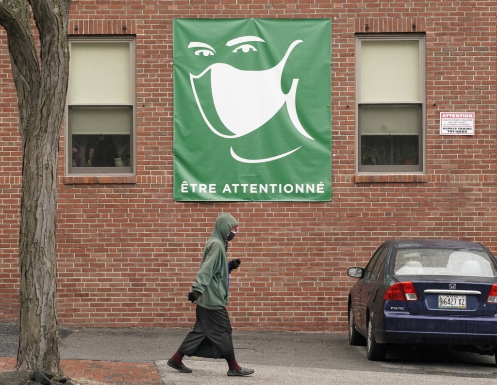 """A woman walks along State Street in Portland on Monday, April 5, 2021 underneath a sign of a person wearing a mask with a French phrase that translates loosely to """"be attentive."""""""