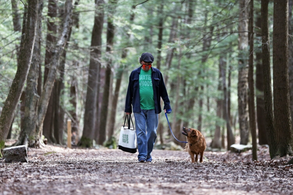 Marc Lesperance walks his dog, Marco, in Baxter Woods on Tuesday. Lesperance argues that the city's new leash rules go against what former Maine Gov. Percival Baxter intended for the land.